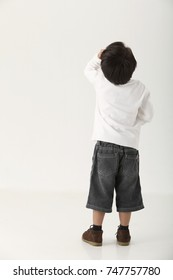 Rear View of a Boy scratching head