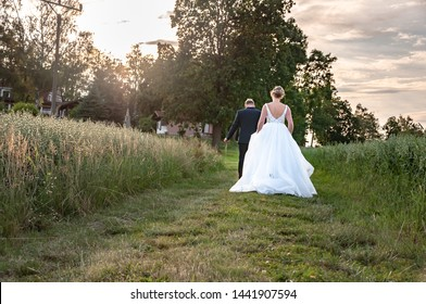 Rear view to bride and grom walking together in nature.