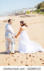 rear view of bride and groom walking on beach