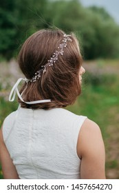 Rear view of bride in simple wedding dress and hairstyle decorated by fancy beaded hair accessory outdoors