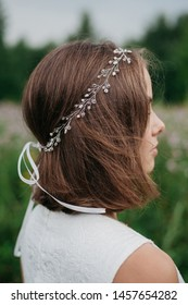 Rear view of bride in simple wedding dress and hairstyle decorated by fancy hair accessory standing in field