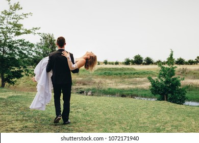 Rear view of bridegroom carrying his bride and walking away at the park. Newlywed couple celebrating marriage outdoors.