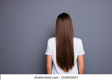 Rear view of brown-haired  young lady with long hair, wearing white t-shirt over grey background, isolated
