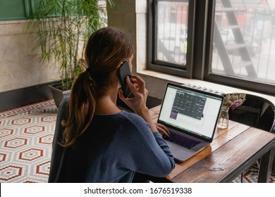 Rear view of brunette business woman working on computer and speaking on phone. Caucasian female working online, internet shopping, checking social network. Home office, flexible way of work concept.