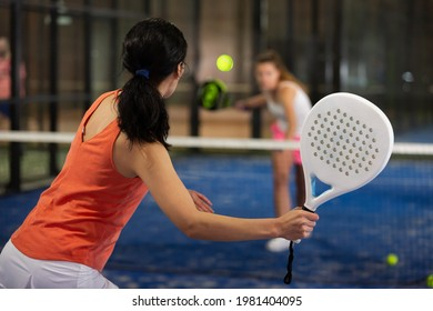 Rear view of brunette girl with white racket playing padel tennis at court