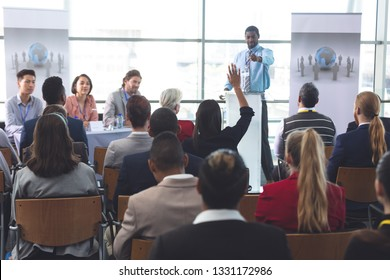 Rear view of brunette mixed race businesswoman raising hand during business seminar in modern office building