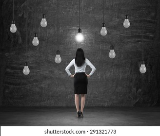 Rear view of the brunette woman in formal clothes who is surrounded by light bulbs as a symbol of the new business ideas.