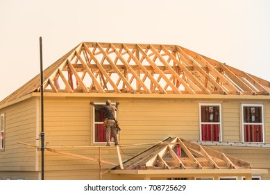 Rear view of builder at eco wooden house construction site near completed suburban home in Humble, Texas, US during sunset. Carpenter on scaffolding installing board of stick built. Labor day concept