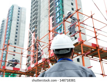 Rear view of builder inspector checking a construction site works.