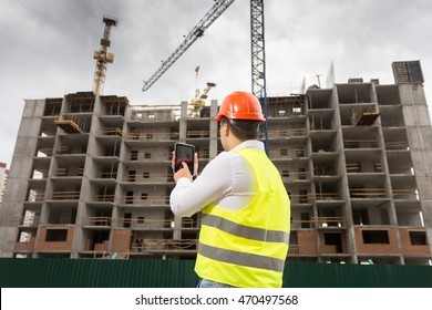 Rear view of building inspector holding digital tablet and inspecting building site