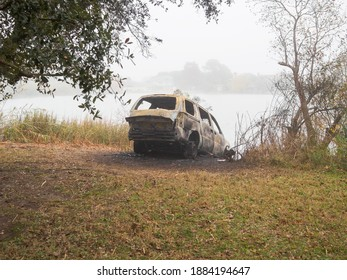 Rear view of burned out car on river bank in New Orleans, Louisiana, USA