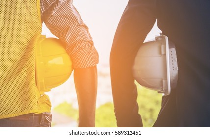 Rear view of Business man and engineer,partner holding construction helmet safety and blueprints looking to success city background