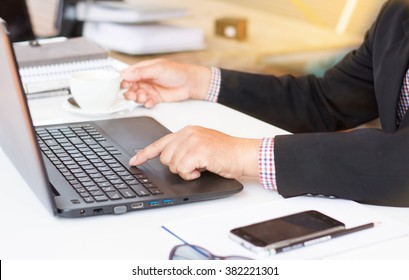 rear view of business man hands busy using laptop at office desk