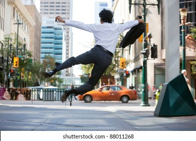 Rear view of business man jumping in air and kicking heals