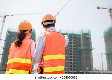 Rear view of business partners at the construction site