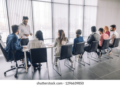 Rear view of business people sitting in a raw and listening a business coach at seminar at spacious modern conference room with panoramic windows