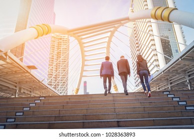 Rear view of business team climbing stairs go to a city. Business concept