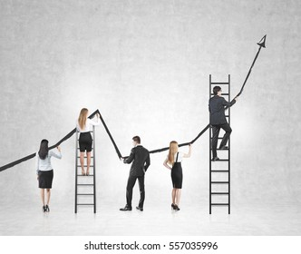 Rear view of a business team drawing a large black growing graph on a concrete wall. Some people are standing on ladders. Mock up