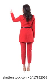 Rear view of business woman in red suit pushing button gesture on touch screen. Full body isolated on white background.