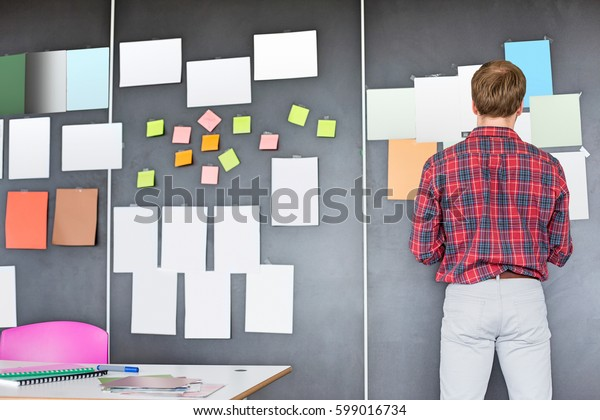 Rear view of businessman analyzing documents on wall at creative office