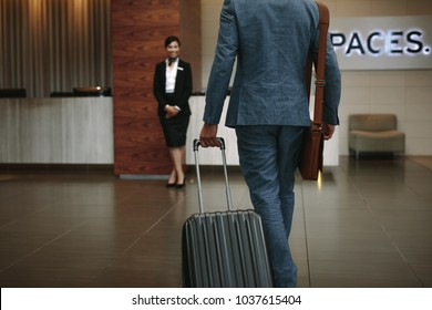Rear view of businessman arriving the hotel with his luggage with female concierge standing in background for welcoming.