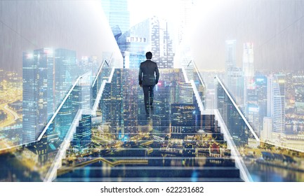Rear view of a businessman ascending a staircase in a city. Night cityscape is in the background. Toned image, double exposure