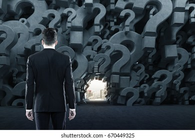 Rear view of a businessman in a black suit standing in an empty room with gray 3d question marks on the walls. There is a way out in the distance. Concept of an answer search. 3d rendering mock up