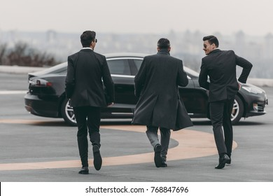 rear view of businessman and bodyguards walking to car at helipad