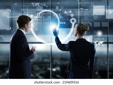 Rear view of businessman and businesswoman touching icon of digital screen