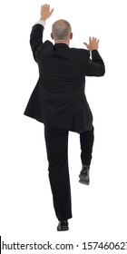 rear view of a businessman climbing isolated on a white background