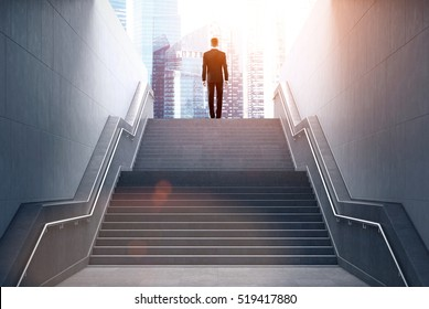 Rear view of a businessman climbing stairs to get to a large city center. Concept of success and appreciation. Toned image