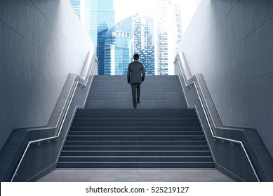 Rear view of a businessman climbing stairs to get to a large city center. Concept of success and appreciation.