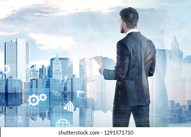 Rear view of businessman with documents looking at modern cityscape with business interface icons in the foreground. Toned image double exposure