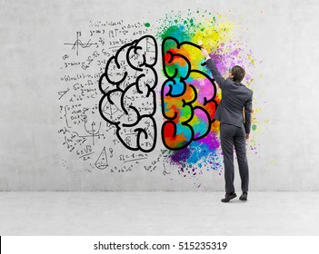 Rear view of a businessman drawing a giant brain sketch with formulas and colors on a concrete wall.