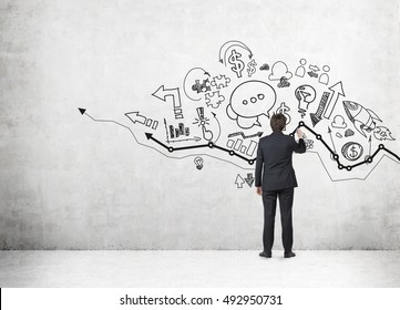 Rear view of businessman drawing sketch on wall with growing graph. Concept of business analysis. Mock up