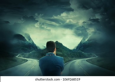 Rear view of a businessman in front of a crossroad, fork junction where a road is splitted in two different ways. Choosing the correct way between left and right, failure or success.Difficult decision