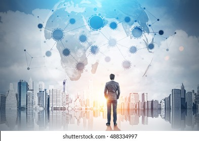 Rear view of businessman with hands in pockets looking at large planet in the sky with startup sketch. Toned image. Double exposure