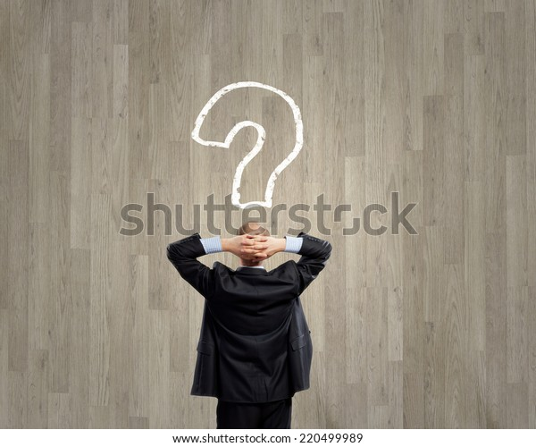 Rear view of businessman looking thoughtfully at question mark above head