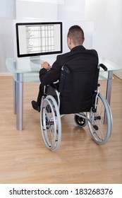 Rear view of businessman on wheelchair using computer in office