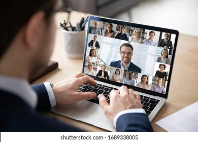 Rear view of businessman speak on web conference with diverse colleagues using laptop Webcam, male employee talk on video call with multiracial coworkers have online meeting briefing from home - Shutterstock ID 1689338005