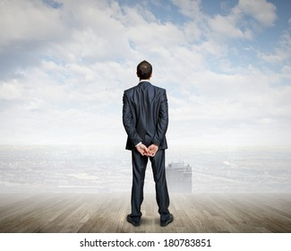Rear view of businessman standing against urban scene