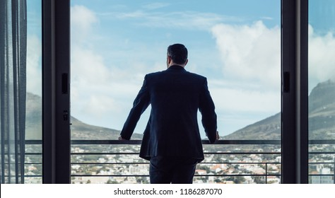 Rear view of businessman standing by hotel room balcony looking at the city view.  Man in business suit looking outside from hotel room.