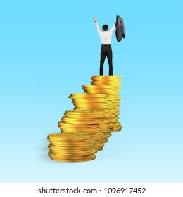 Rear view of businessman standing and cheering on top of golden coins stacks, isolated on blue background, concept of business financial growth success.