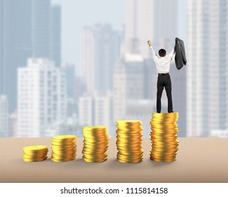 Rear view of businessman standing and cheering on top of golden coins stacks, with city buildings skyscrapers background, concept of business financial growth success.