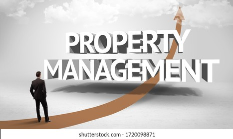Rear view of a businessman standing in front of PROPERTY MANAGEMENT inscription, successful business concept
