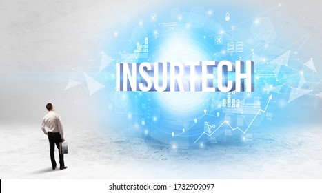 Rear view of a businessman standing in front of INSURTECH inscription, modern technology concept