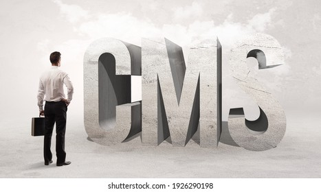 Rear view of a businessman standing in front of CMS abbreviation, attention making concept