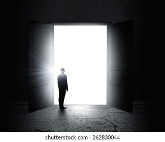 Rear view of businessman standing in light of opened door