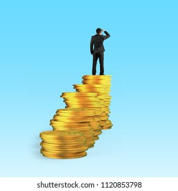 Rear view of businessman standing on top of golden coins stacks and looking far into the distance, isolated on blue background, concept of business financial growth success.