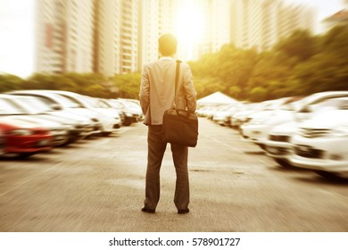 Rear view businessman standing at open car park, looking away with beautiful sunlight.